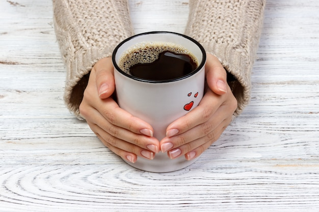 Woman's hands holding cup with coffee, top view