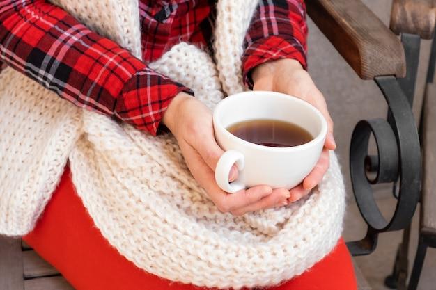 Женские руки, держа чашки чая или кофе, одетые в красно-белую праздничную одежду.