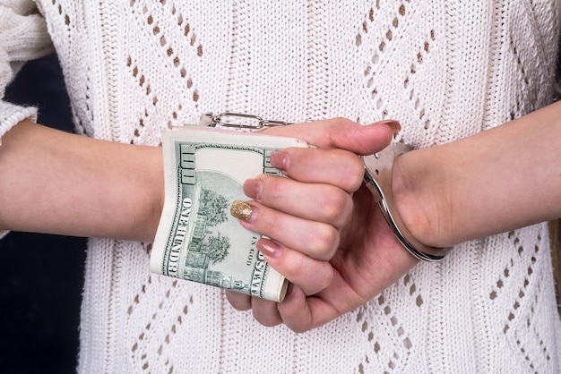Woman's hands holding dollar banknotes in handcuffs behind back