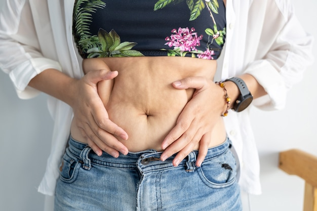 Woman's hands holding excessive belly fat