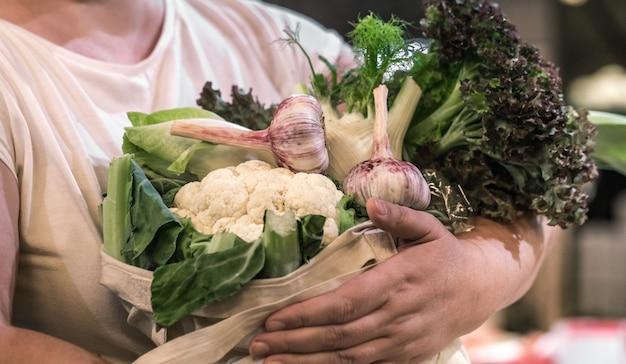 週末のファーマーズマーケットで新鮮な熟した有機ブロッコリー、綿の袋に緑と野菜のサラダを持っている女性の手