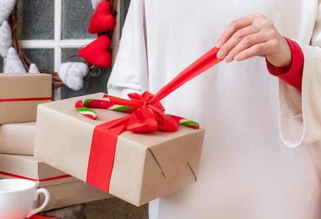 Женские руки держат подарочную коробку с красной лентой
