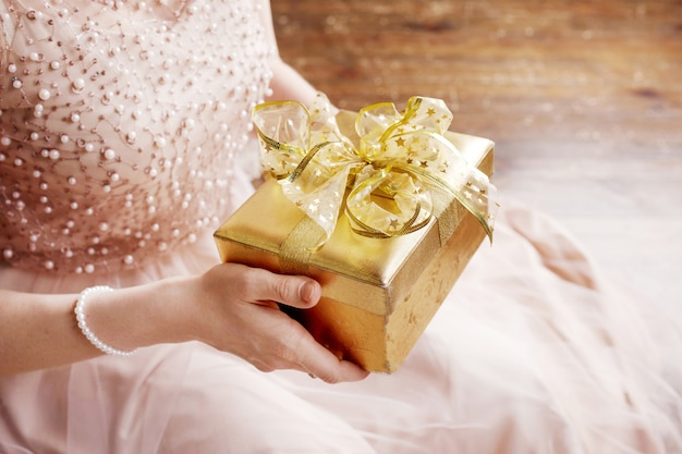 Woman's  hands holding gold gift box.