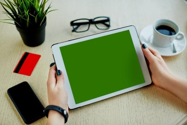 녹색 태블릿 신용 카드, 안경, 휴대 전화 및 테이블, 프리랜서 개념, 온라인 쇼핑, 평면 누워 커피 한잔 들고 여자의 손.