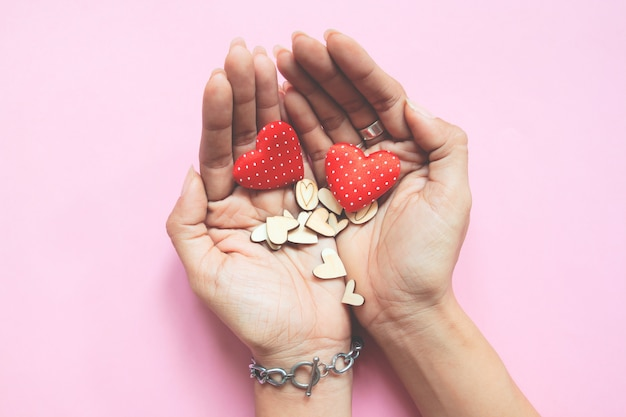 Woman's hands holding hearts. love and valentines concept on pink background
