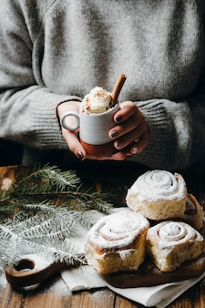 Woman's hands holding hot cocoa with whipped cream and cinnamon stick