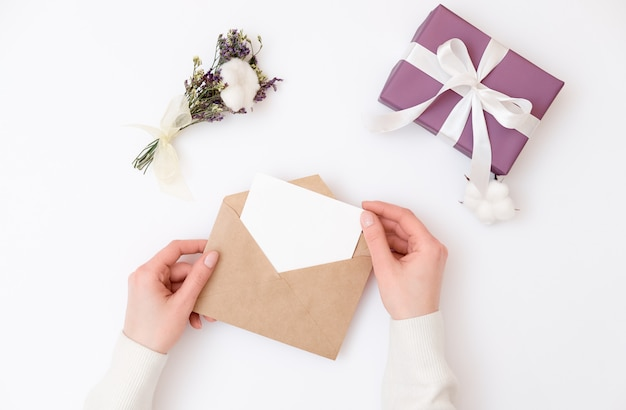 Woman's hands holding kraft envelope with blank wedding invitation card