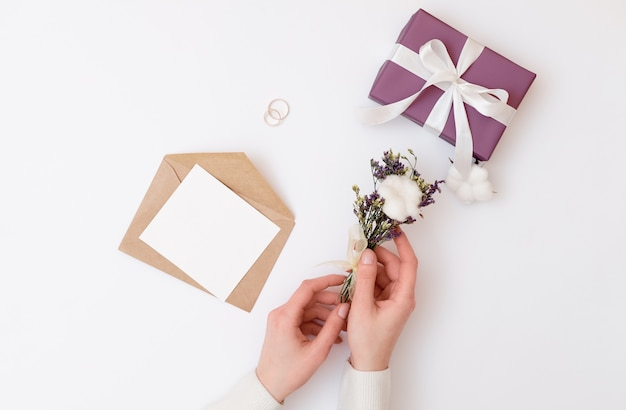 Woman's hands holding kraft envelope with blank wedding invitation card.