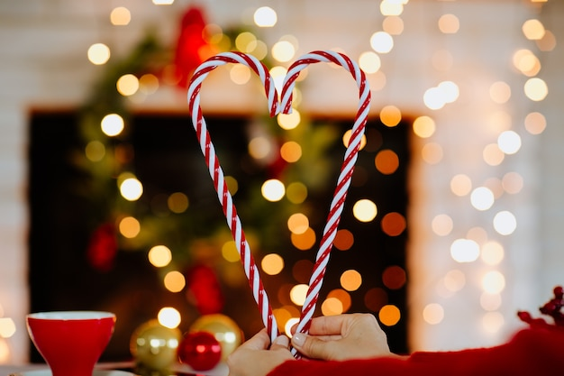 Woman's hands holding lollipops like a heart symbol against christmas background.