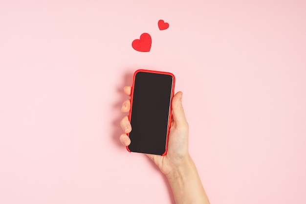 Woman's hands holding mobile phone with blank screen with heart shape