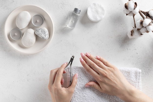 Woman's hands holding nail clippers and cut the cuticle. hand care, deep manicure. white stone wall, top view. horizontal image