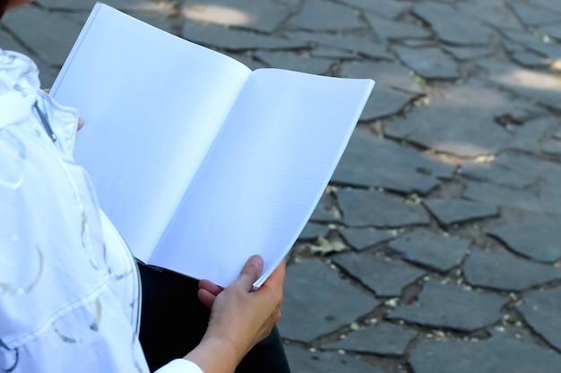Женские руки держат ноутбук с местом для текста на фоне каменной дороги