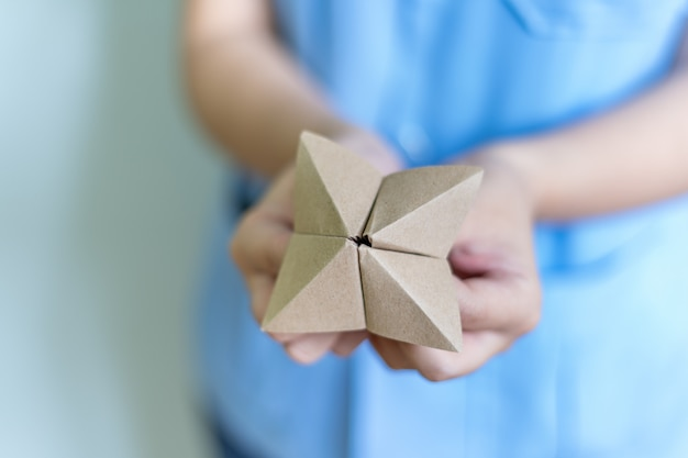 Woman's hands holding a paper fortune teller on blue background