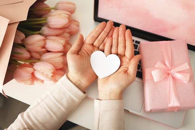 紙のハートカードを保持している女性の手。ピンクの背景、バレンタインデーのコンセプト。背景にチューリップの花とピンクのギフトボックス。レディースホームデスク。