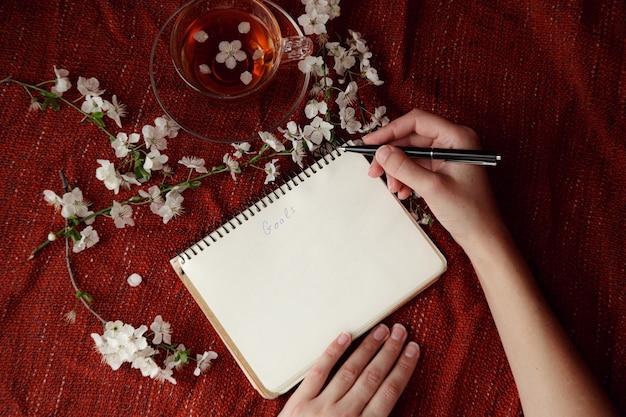 Женские руки, держа ручку и спиральный блокнот как макет для вашего дизайна. красный фон, плоский стиль. идея и концепция весны, перемен, загадывания желаний и постановки целей