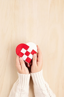 Женские руки держат красное и белое сердце
