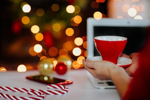 マシュマロとコーヒーの赤いカップを保持している女性の手