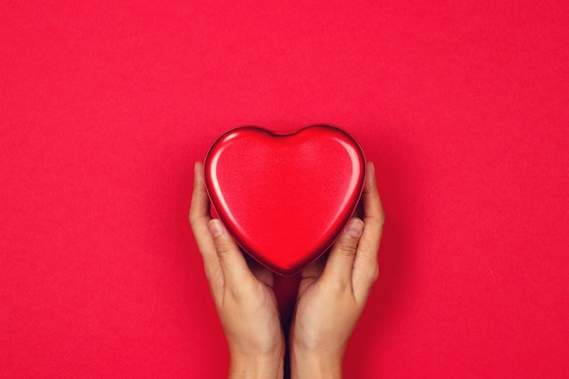Woman's hands holding the red heart on a red background. valentine.