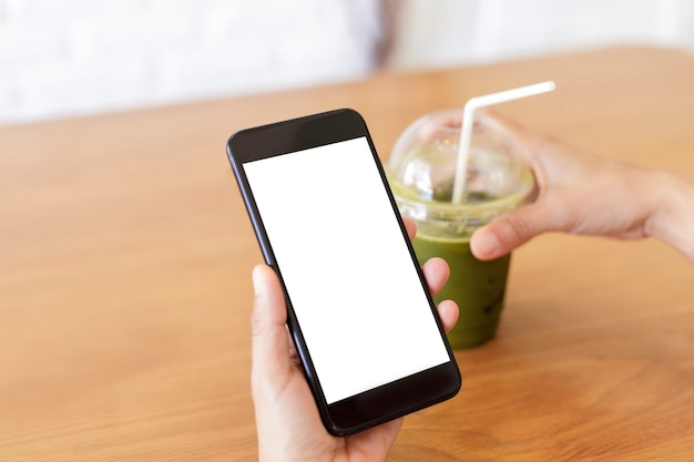 Woman's hands holding smartphone and beverage in cafe