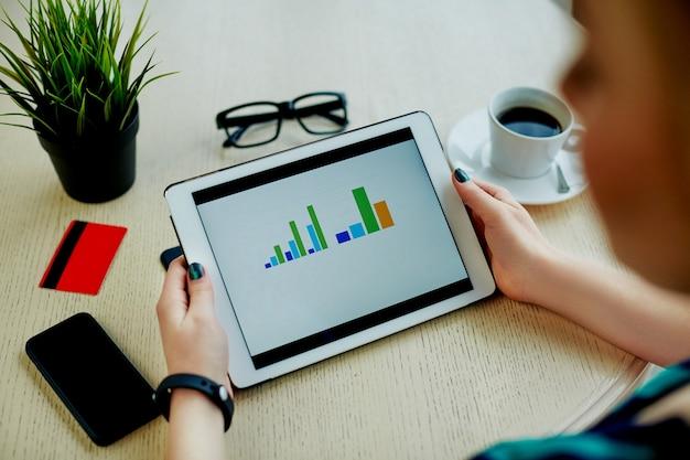 히스토그램, 신용 카드, 안경, 휴대 전화 및 테이블, 프리랜서 개념, 온라인 쇼핑에 커피 한잔으로 태블릿을 들고 여자의 손.