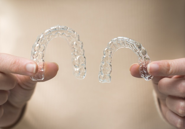 Woman's hands holding two side lit transparent retainers on beige wall