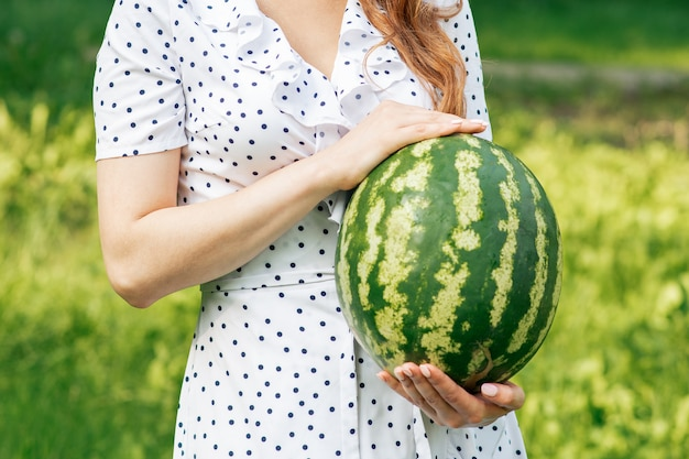 Woman's hands holding a watermelon outdoors
