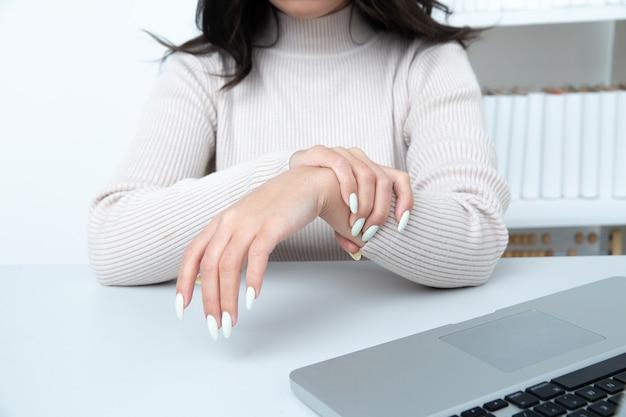 사무실에서 여자의 손입니다. 관절염 개념입니다.