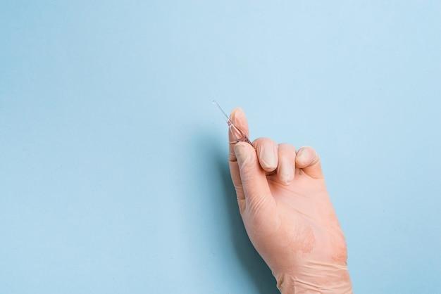Руки женщины в медицинских перчатках держит ампулу вакцины на светло-синем фоне.