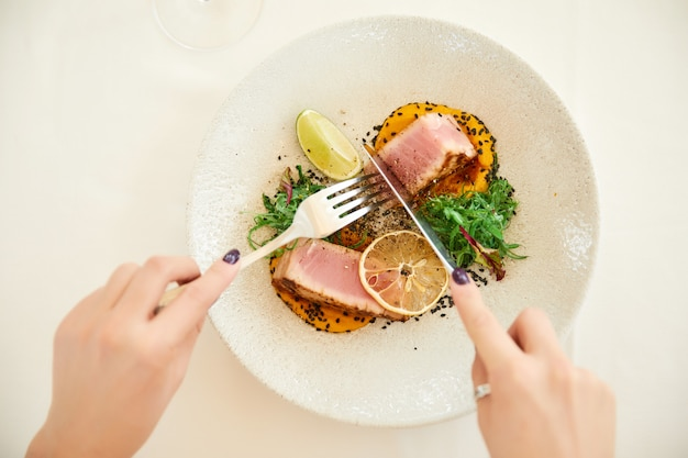 Woman's hands is holding cutlery over a tuna dish