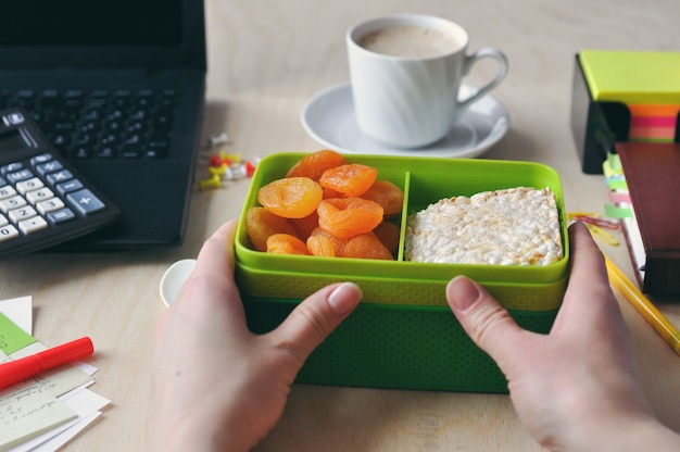 A woman's hands is holding lunch box next to a cup of coffee at the desk close-up. study and and working concept