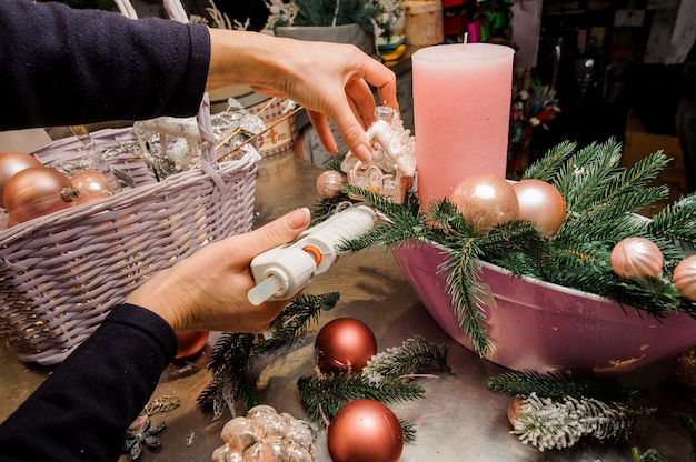Woman s hands making a beautiful christmas decoration composition