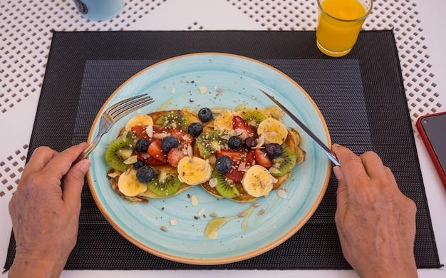 朝食、新鮮なフルーツ、蜂蜜のための古典的なアメリカのパンケーキとテーブルの上の女性の手。健康的な食事の概念