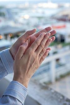 코로나 바이러스와의 싸움을 위해 의료진을 박수하기 위해 발코니에 여자의 손