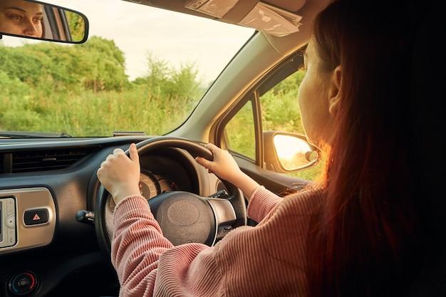 운전대에 있는 여성의 손, 운전사가 차를 운전하고 있습니다.