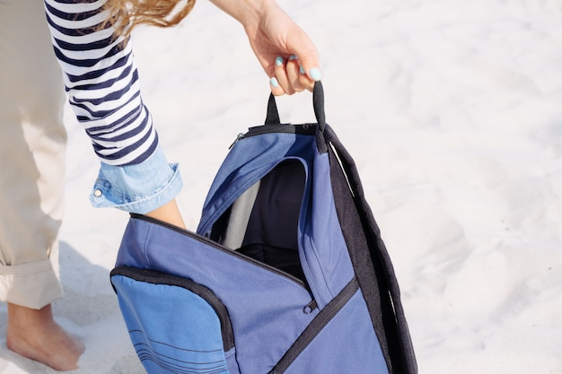 Woman's hands opened the blue backpack and pulled out stuff for a picnic on the beach