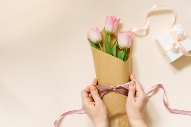 女性の手は茶色のエコペーパーとサテンのリボンを使用して新鮮なチューリップの花束を詰めます