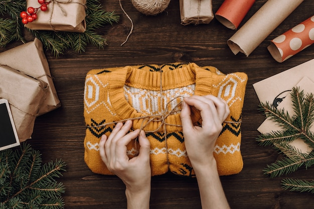 Woman's hands packing knitted sweater as present on dark wooden table