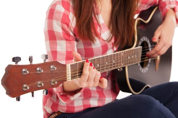 Руки женщины, играя на акустической гитаре, крупным планом. полный прибор видно. изолированные на белом фоне