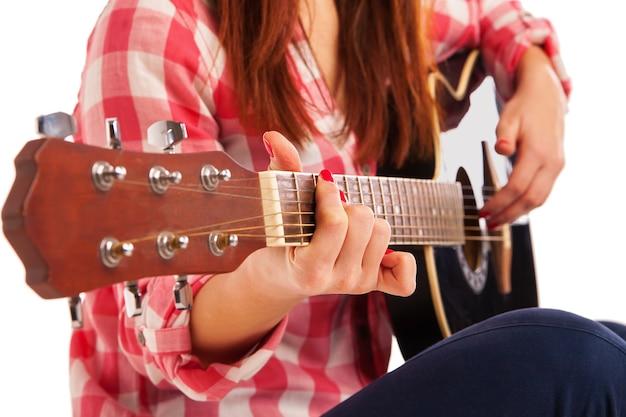 Руки женщины, играя на акустической гитаре, крупным планом. изолированные на белом фоне
