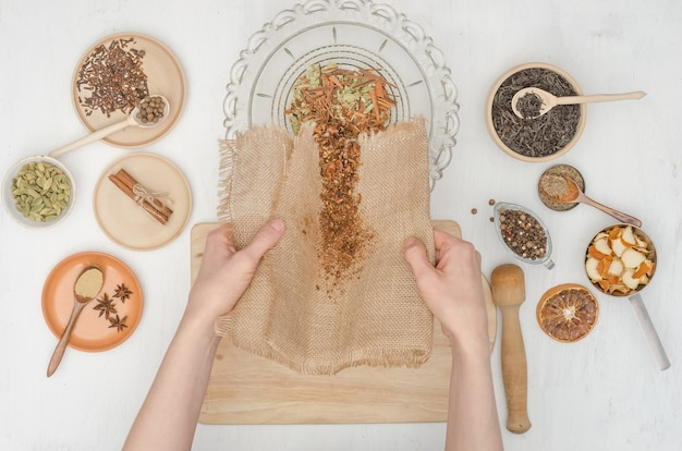 Woman's hands preparing indian masala tea with spices