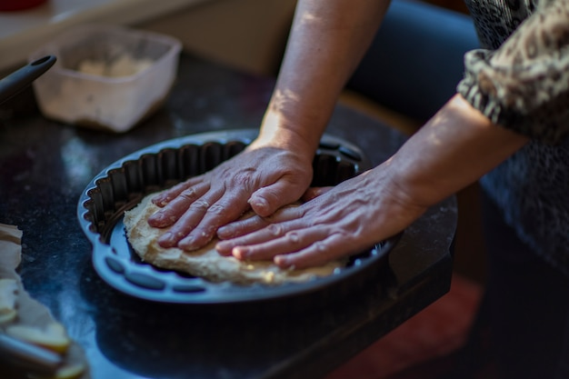 Woman's hands rolling dough in baking dishes