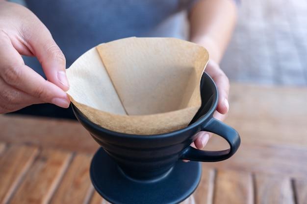 빈티지 나무 테이블에 드립 커피를 만들기 위해 필터를 설정하는 여자의 손