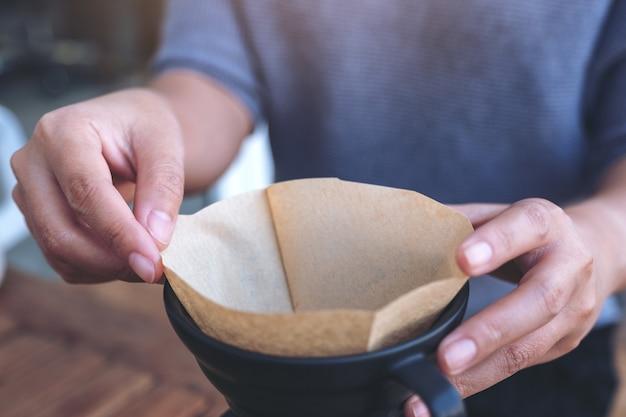 ヴィンテージの木製テーブルにドリップコーヒーを作るためにフィルターを設定する女性の手