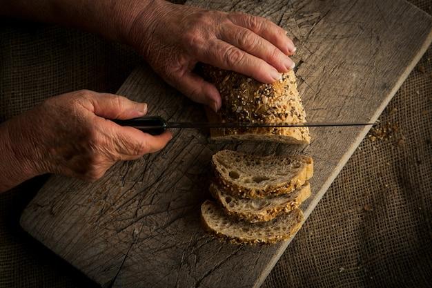 나무 커팅 보드에 집에서 만든 밀 빵을 자르는 여자의 손.