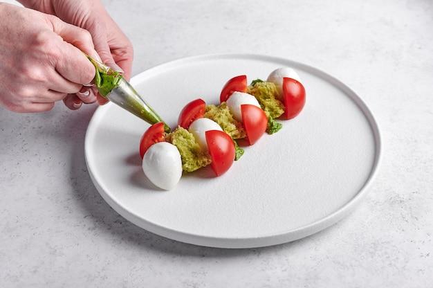 Женские руки выдавливают соус песто к восхитительному итальянскому салату капрезе со спелыми помидорами, свежим садовым базиликом и сыром моцарелла.