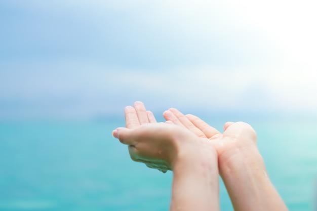Woman's hands on a sunny bach