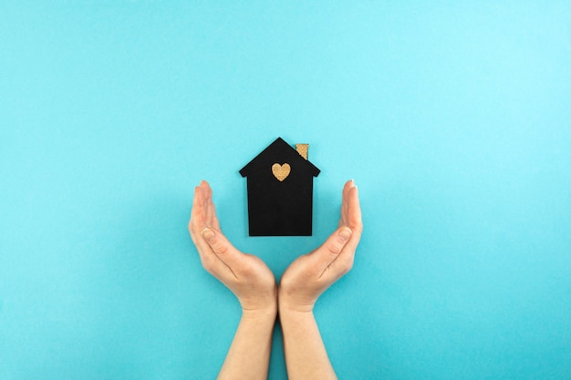 Woman's hands surround a mock-up of a dark house on a blue background