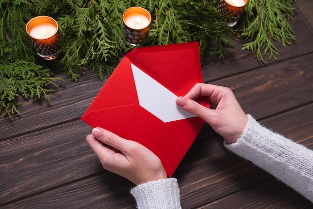 Руки женщины достают рождественское письмо из красного конверта. рождественский дизайн.