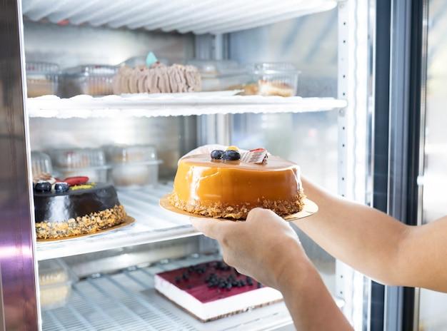 제과점에서 케이크를 들고 있는 여성의 손