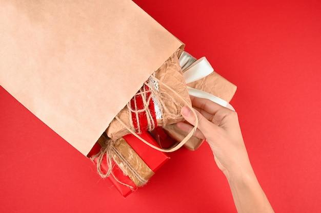 Руки женщины принимают подарок из бумажного пакета